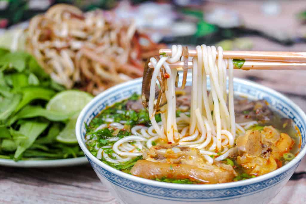 chopsticks lifting noodles out of a bowl of Spicy Vietnamese Beef Noodle Soup (Bún bò Huế)