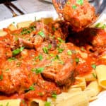 a large plate of rigatoni ragu, with a fork and spoon holding up a meatball in the upper right hand corner, from Carmine's