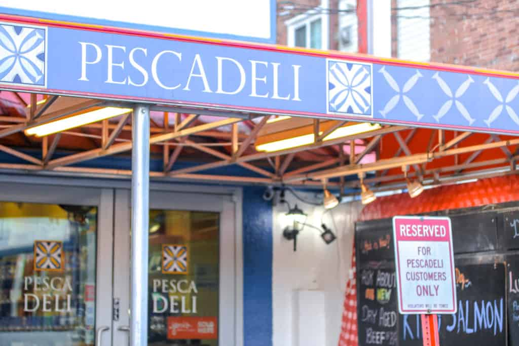 "storefront with blue awning that says ""pescadeli"""