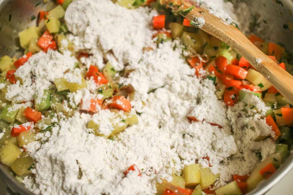 flour on top of vegetables for pot pie