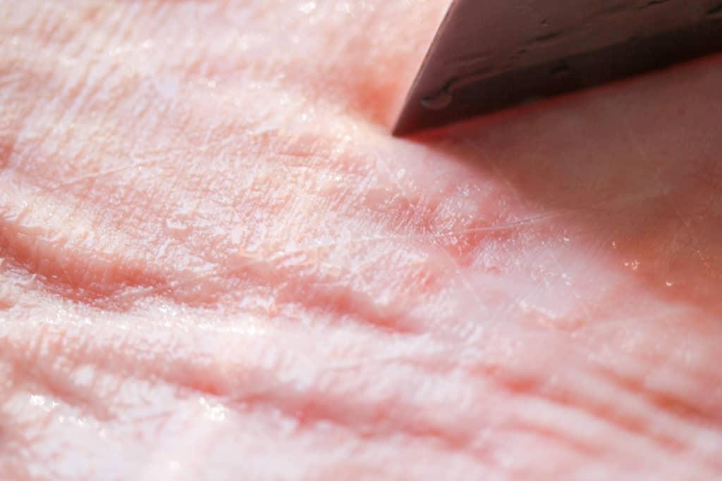 knife scoring pork belly skin