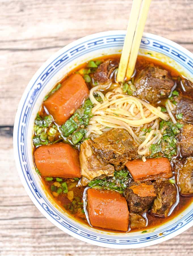 blue and white bowl filled with noodles, stew with beef and carrots. A pair of chopsticks is sticking into the noodles