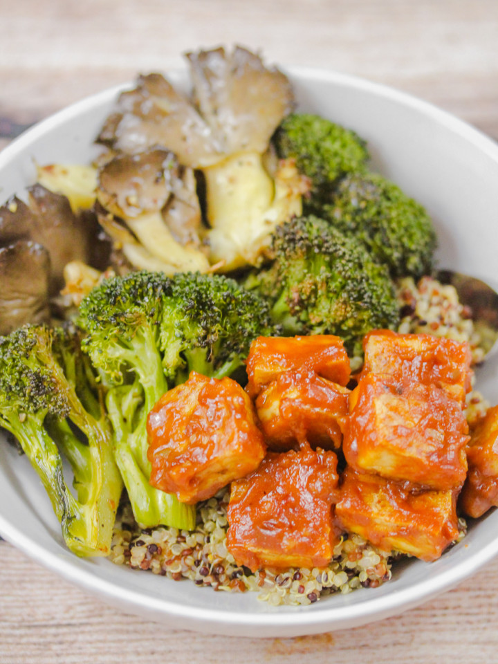White bowl with tri-color quinoa, tofu cubes coated in peanut sauce, roasted broccoli and oyster mushrooms