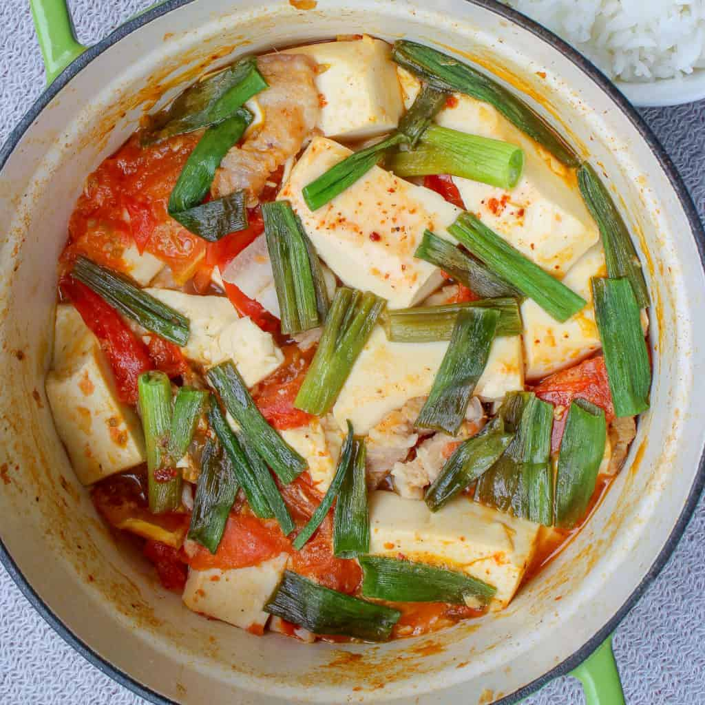 soft tofu braised in a pot with tomato and pork belly