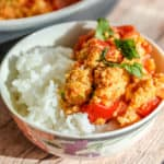 small white bowl with steamed rice and scrambled eggs with tomato piled on top