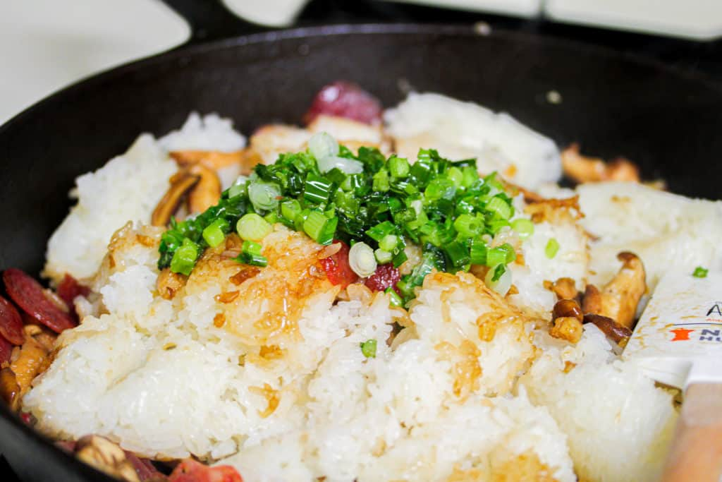 unmixed white sticky rice with green onions on top