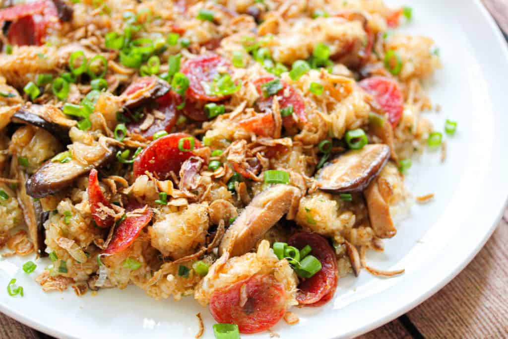 A close up shot partially showing a white plate. Brown sticky rice with chinese sausage, sliced mushroom and green onion are mixed through the rice
