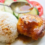 A Gà Roti plate: A white plate with one glazed chicken thigh, a round mound of rice, and cucumbers and tomatoes