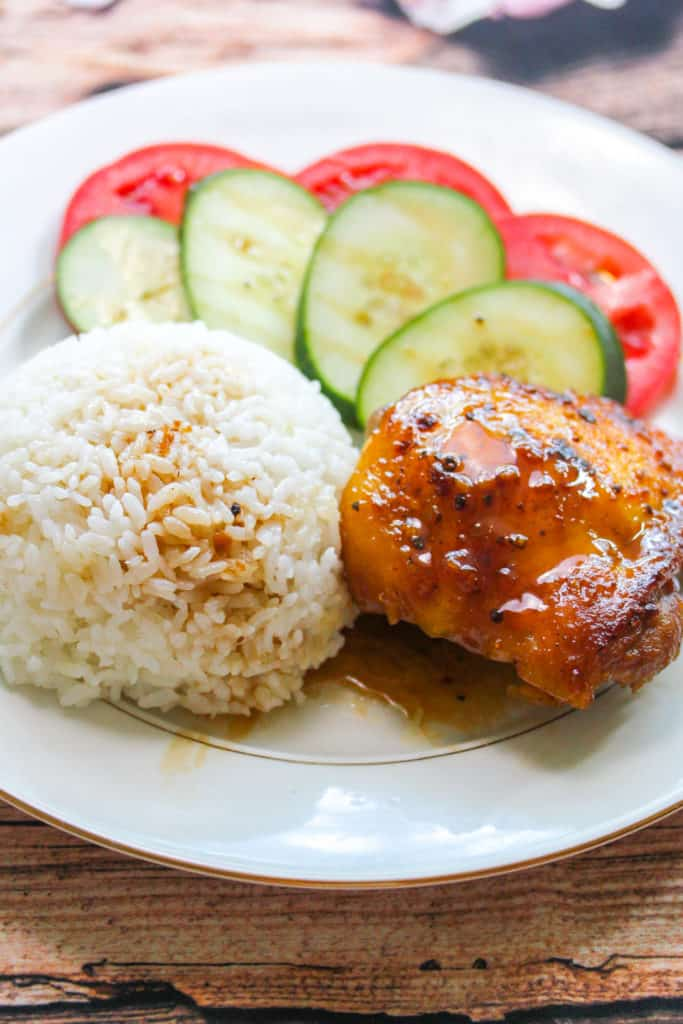 White plate with gold trim. On the plate is a chicken thigh (Gà Roti) with brown glaze, a round mound of rice, slices of tomato with slices of cucumber layered on top of the tomato.