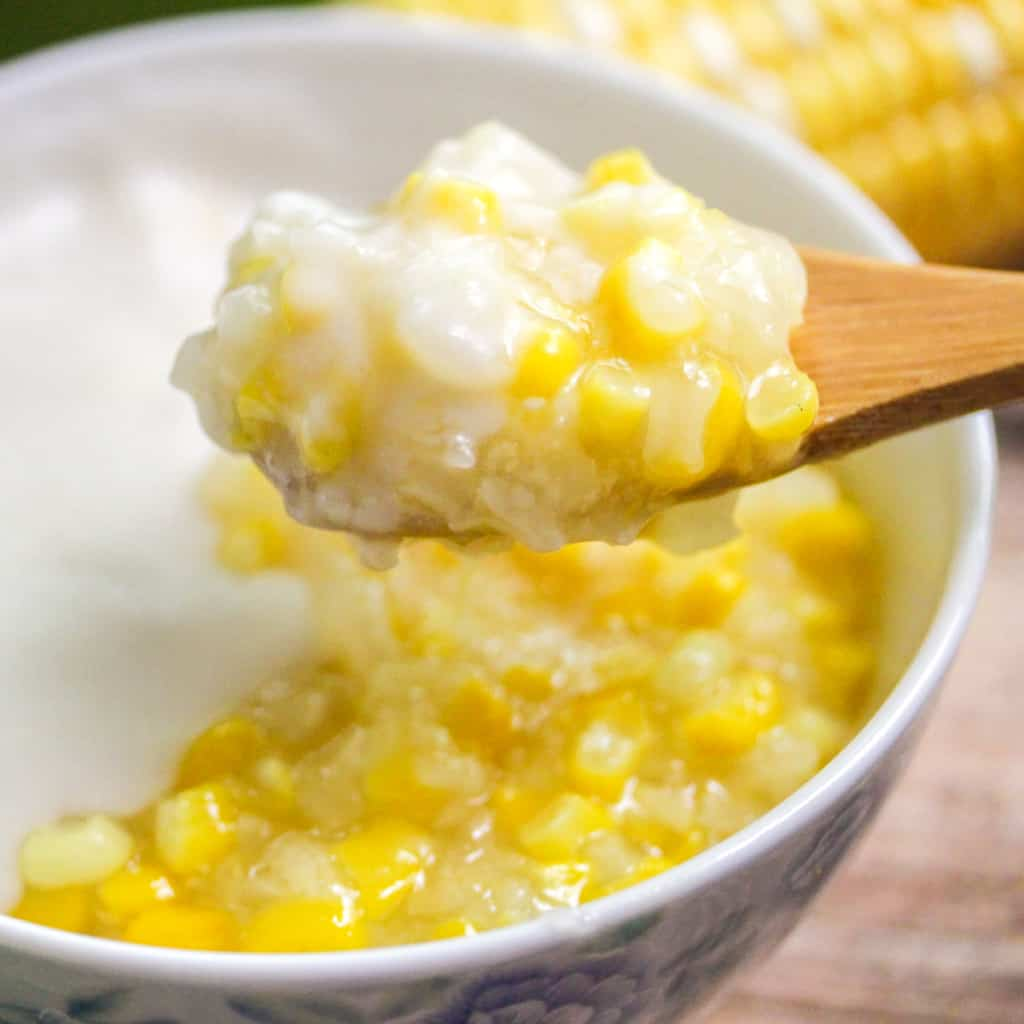 A wooden spoon with a scoop of rice and sweet corn pudding topped with coconut milk