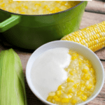 Bowl of sweet corn pudding with green dutch oven in the background