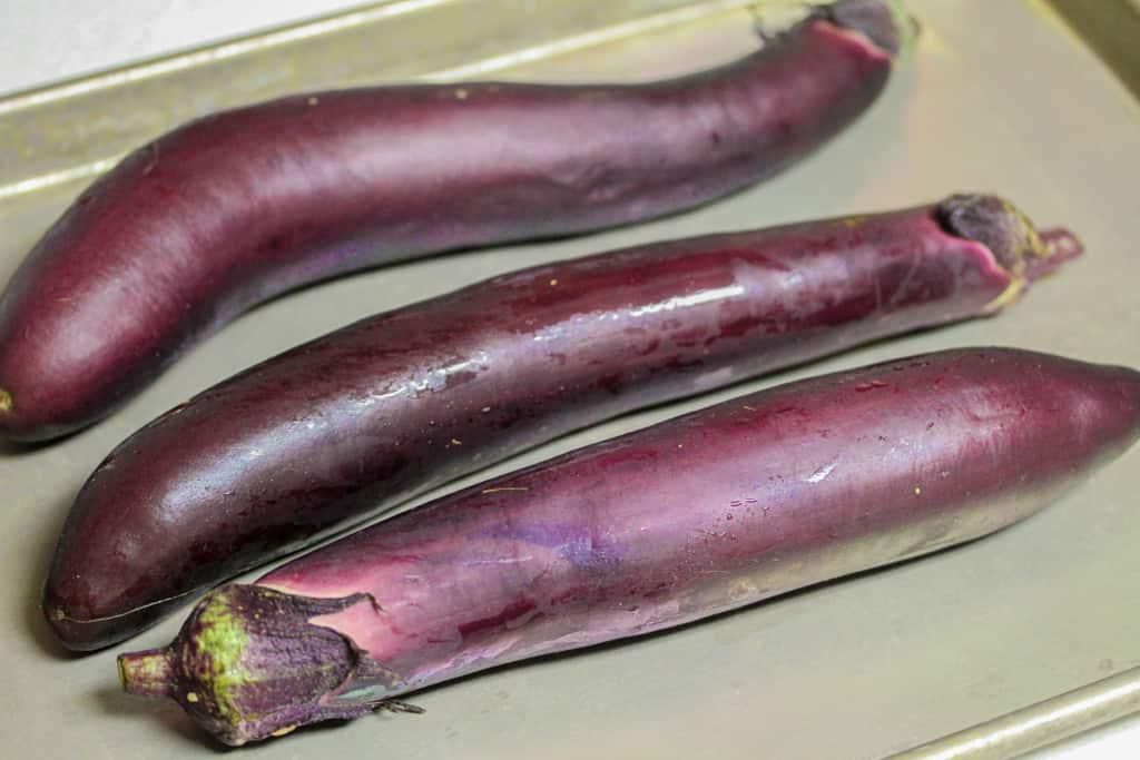 three japanese eggplants on a sheet pan