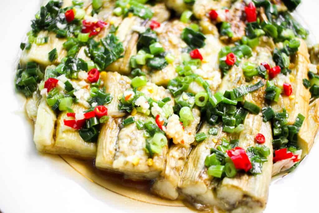 A plate of grilled eggplant segments with scallions and chilis