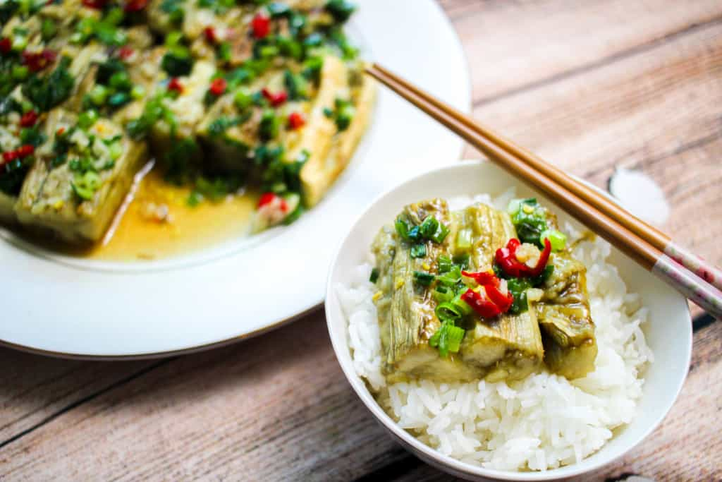 small bowl with grilled eggplant, scallions and chilis in front of a plate of eggplant