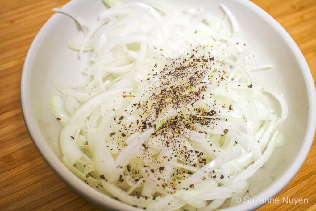 thinly sliced onions sprinkled with black pepper in a bowl