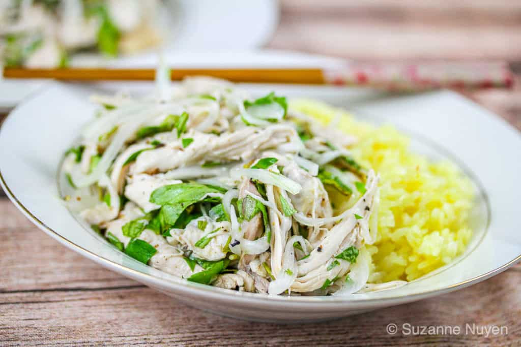 A bowl of shredded chicken salad with yellow sticky rice