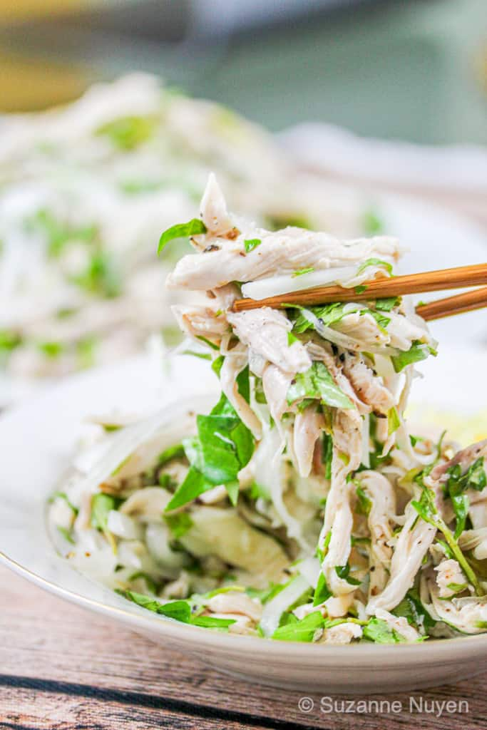 chopsticks holding up shredded chicken salad from a white saucer