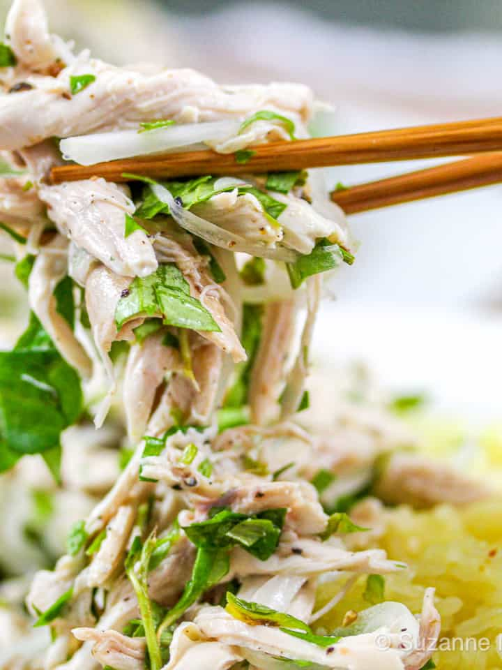 Chopsticks holding up shredded Vietnamese Chicken Salad (Gà Bóp)