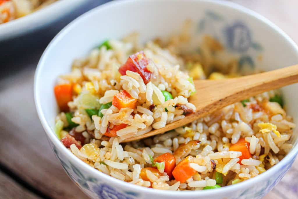 A wooden spoon scooping fried rice out of a bowl