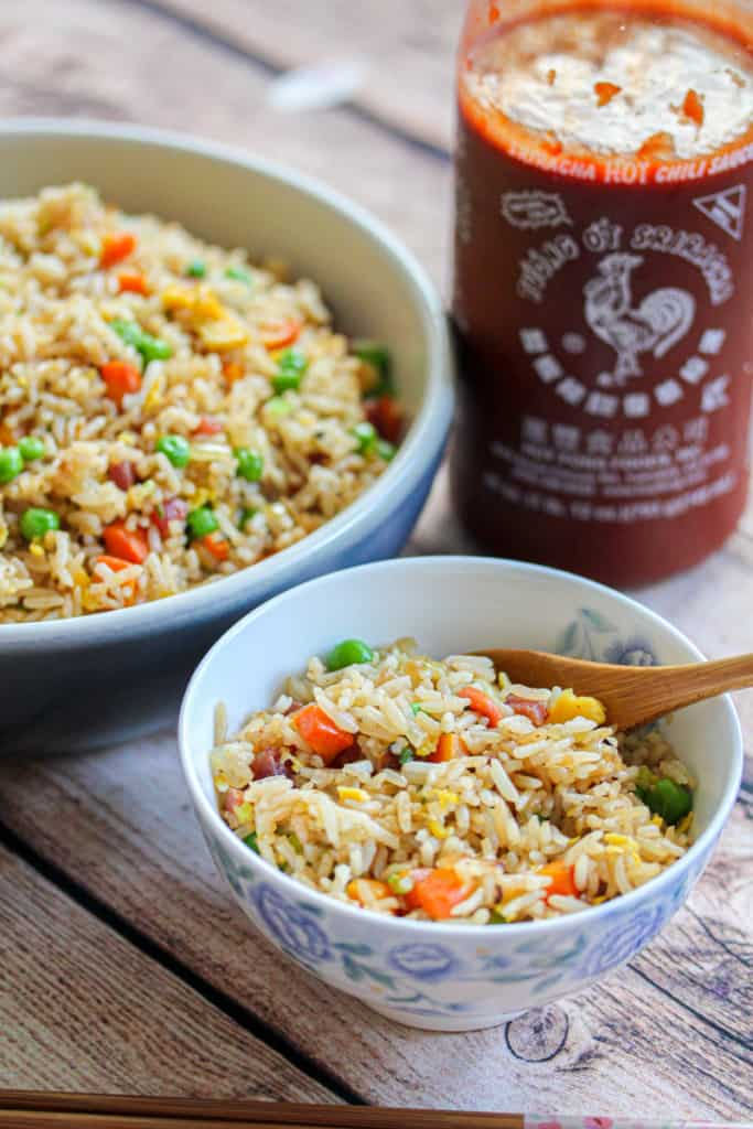 A small bowl of fried rice in front of a larger bowl of fried rice and a jar of Sriracha