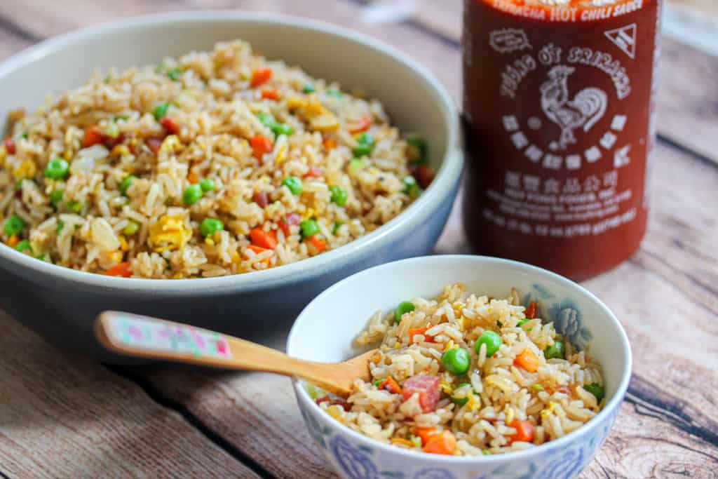 Horizontal version of A small bowl of fried rice in front of a larger bowl of fried rice and a jar of Sriracha