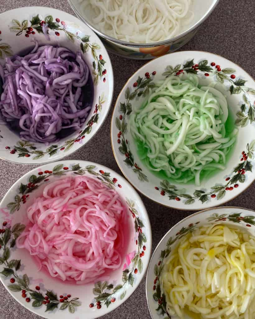 five bowls of died coconut shreds for Mứt Dừa in purple, green, pink, yellow and white