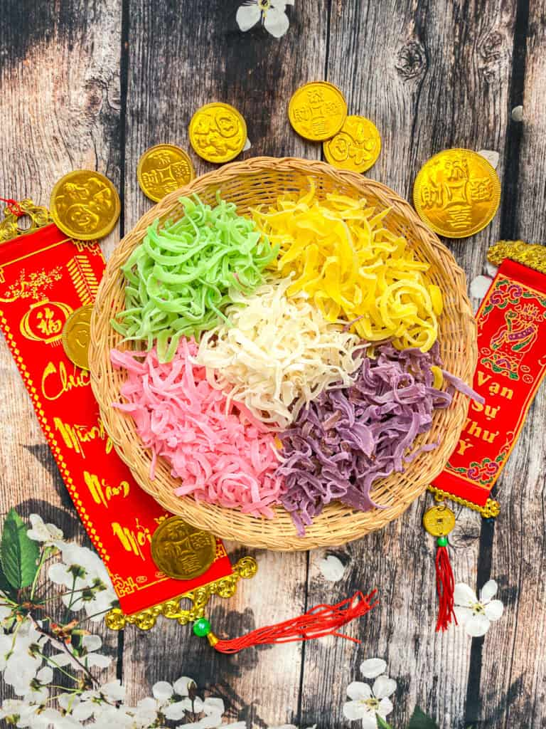 green, yellow, pink, purple and white Mứt Dừa, or coconut candy, on a wicker plate with lunar new year signs around it
