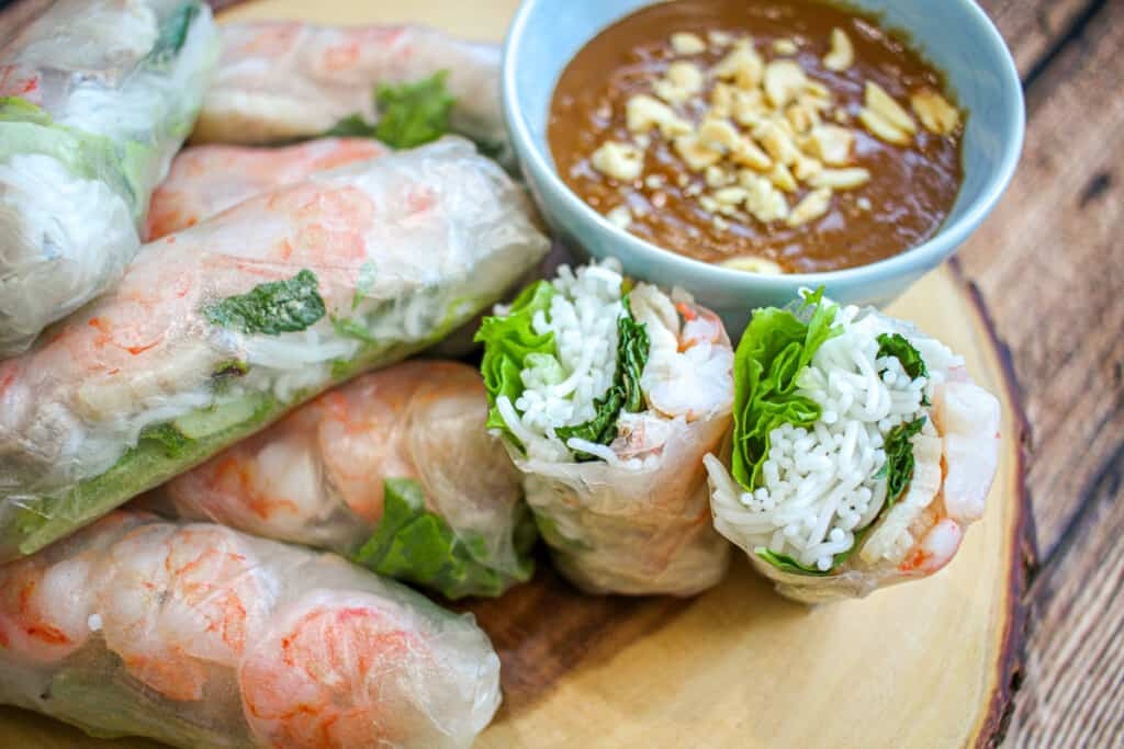 A shrimp and pork spring roll cross section next to a small bowl of peanut sauce