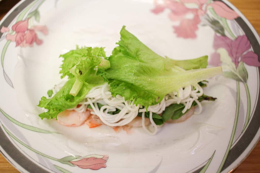 a rice paper layered with shrimp, pork, herbs, noodles and lettuce