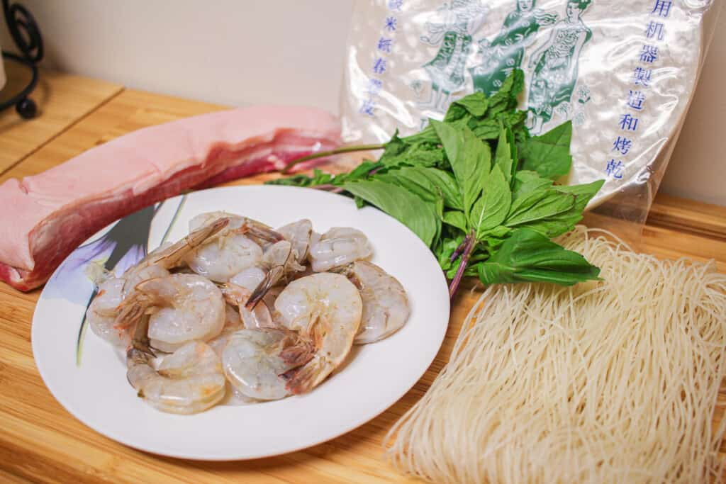 raw shrimp, raw pork bellt, herbs and dry vermicelli noodles on a wooden board