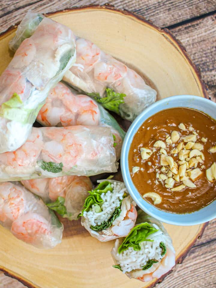 Shrimp and pork spring rolls (gỏi cuốn) on a round wooden board with a blue bowl filled with peanut sauce