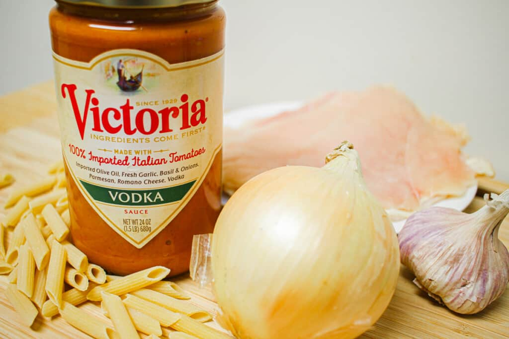 A jar of Victoria Pasta Sauce, an onion, a bulb of garlic, and dry penne pasta on a wooden board