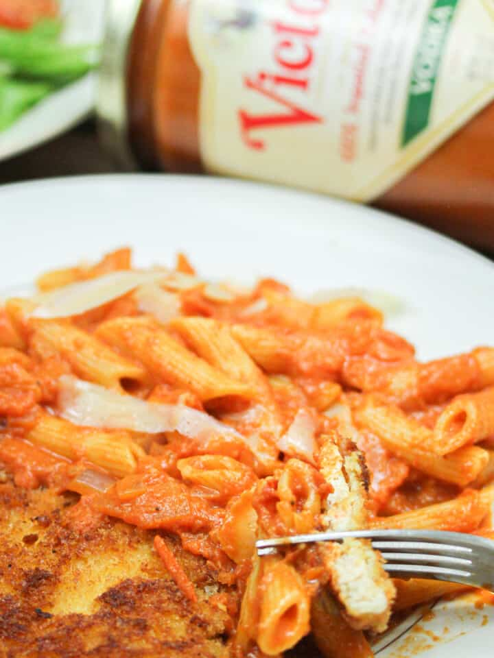 A fork digs into a plate of penne alla vodka