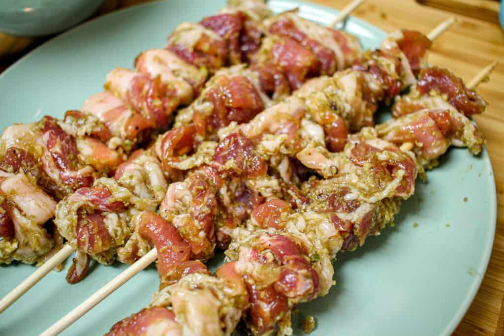 Raw marinated pork on wooden skewers.