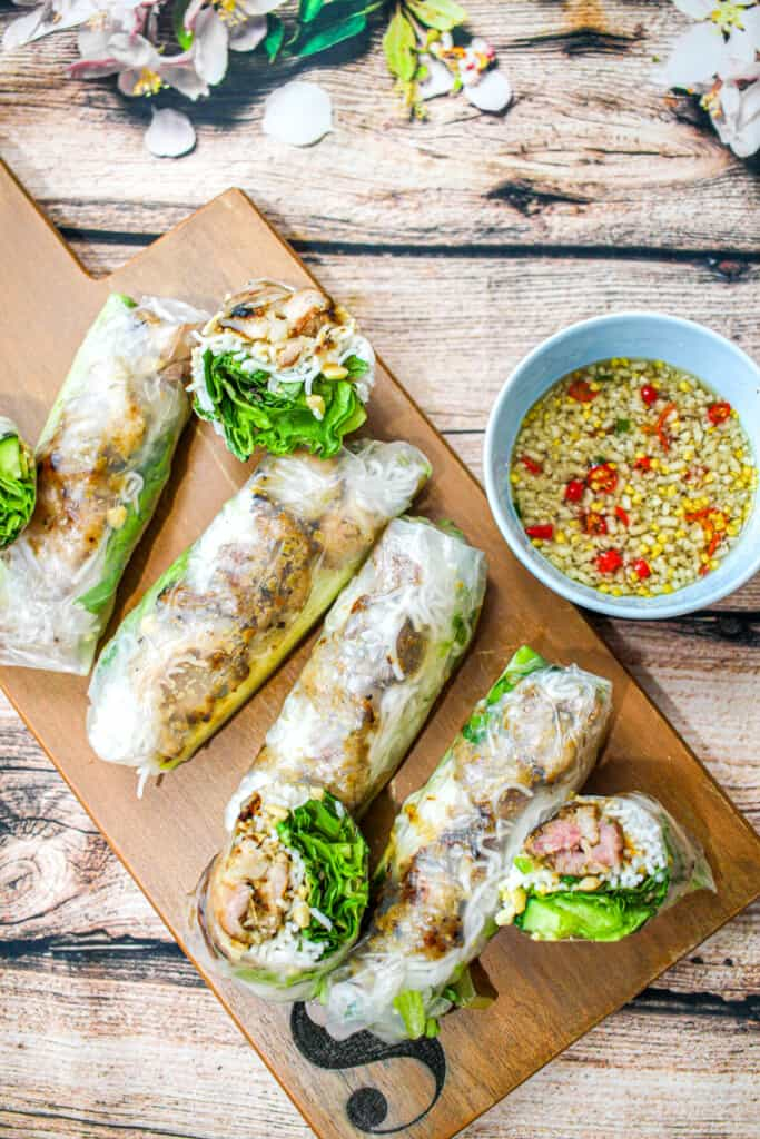 A birds eye view of One grilled pork spring roll cut in half placed next to three whole grilled pork spring rolls.