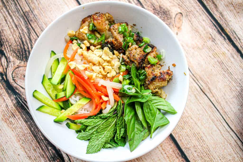 A white bowl with noodles, grilled pork, herbs, cucumbers and pickled vegetables.